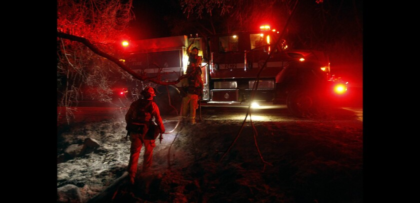 A Cal Fire crew head back to their fire truck as they do mop up work after a fire.