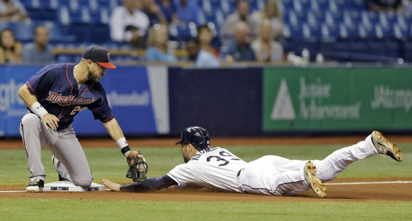 Minnesota Twins' Trevor Plouffe, left, tags out Tampa Bay Rays' Kevin Kiermaier at third base during the third inning of a baseball game Wednesday, Aug. 26, 2015, in St. Petersburg, Fla. Kiermaier was out trying to advance on a fly out by Rene Rivera. (AP Photo/Chris O'Meara)