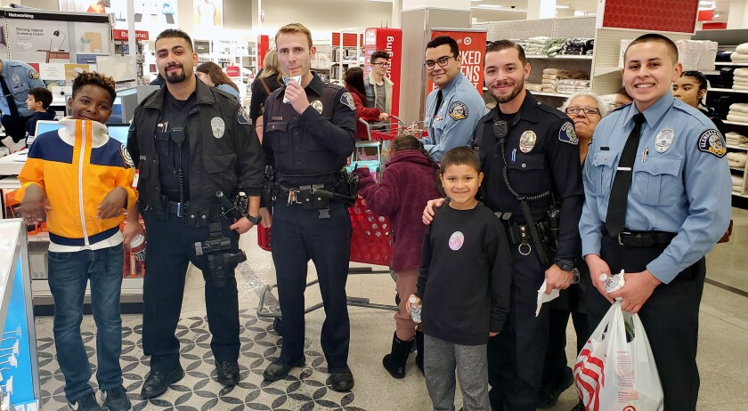 From left to right: Sebastien Phillips, Officer Vlad Akopian, Officer Mark Newborg, Police Explorer Fabrizzio Escobar, Kai Gonzalez, Officer Ian Torley and Police Explorer Jimmy Alfaro take part in the Glendale Police Officers' Assn.'s Shop with a Cop event at the Glendale Galleria Target on Friday, Dec. 6.