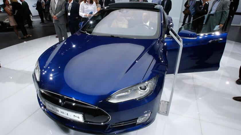 En imagen de archivo, los visitantes se reúnen en torno al auto eléctrico Tesla Model S en una Exhibición Automotriz Internacional. Tesla Motors negó el viernes 10 de junio las acusaciones de problemas de seguridad en las suspensiones de sus vehículos. (AP Foto/Mark Schiefelbein, archivo)