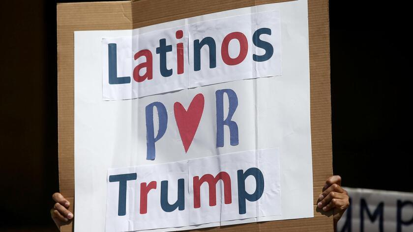 Un hombre sostiene un cartel durante un mitin entre cerca de un centenar de partidarios latinos de Donald Trump, frente al Ayuntamiento de Anaheim, el 28 de agosto de 2016.