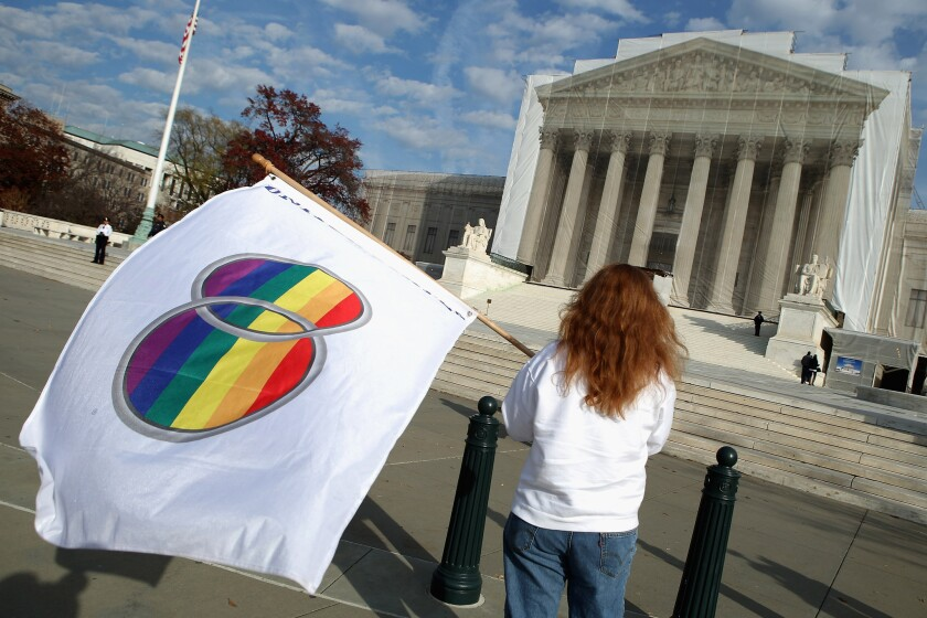 A same-sex marriage proponent holds a gay marriage pride flag while standing in front of the Supreme Court.