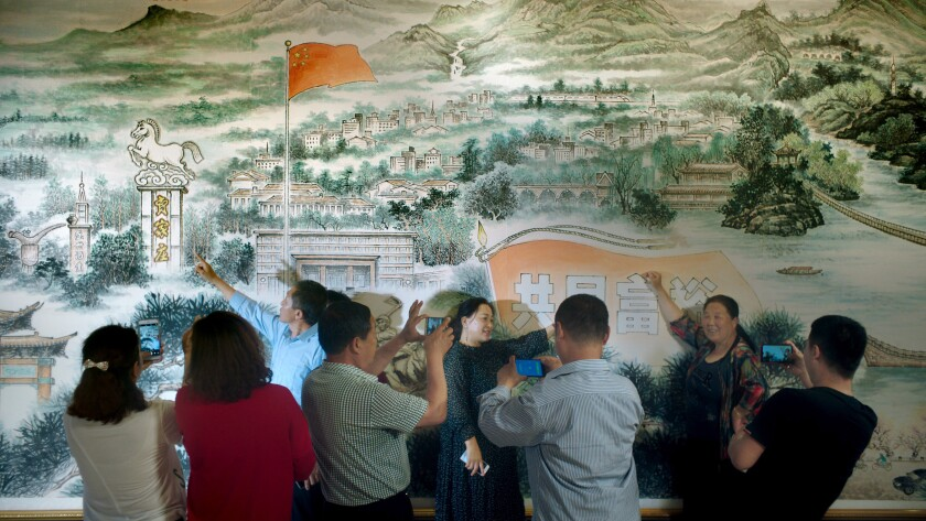 People point at a mural while bystanders snap photos.