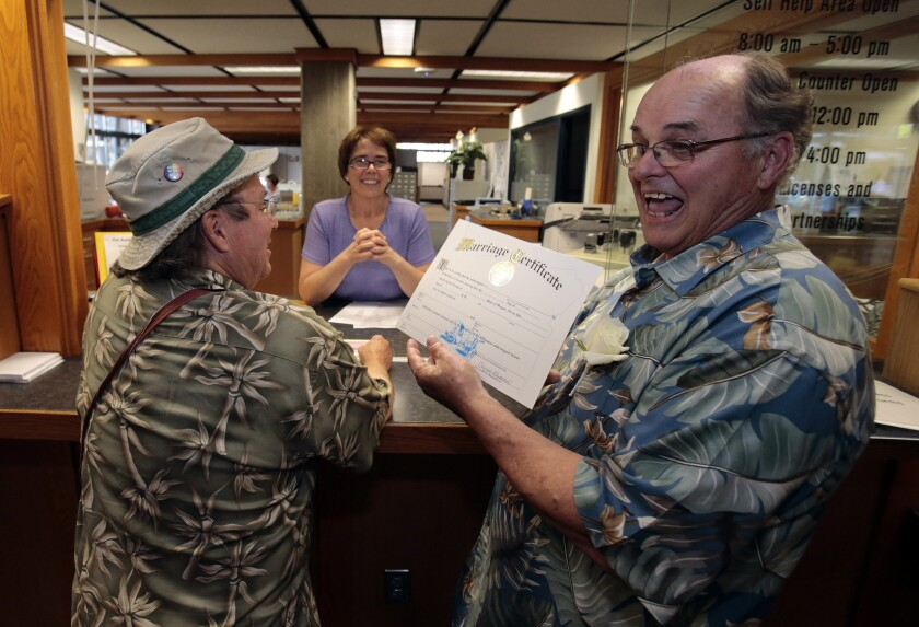 Bruce Carlson, right, shows off his ceremonial marriage license to wed his partner, Matt Friday, left, at the Lane County courthouse in Eugene, Ore. The U.S. Supreme Court on Wednesday refused to halt same-sex weddings in Oregon as long as a federal appeals court is considering a case in which a group has sued to restore a ban on such weddings.