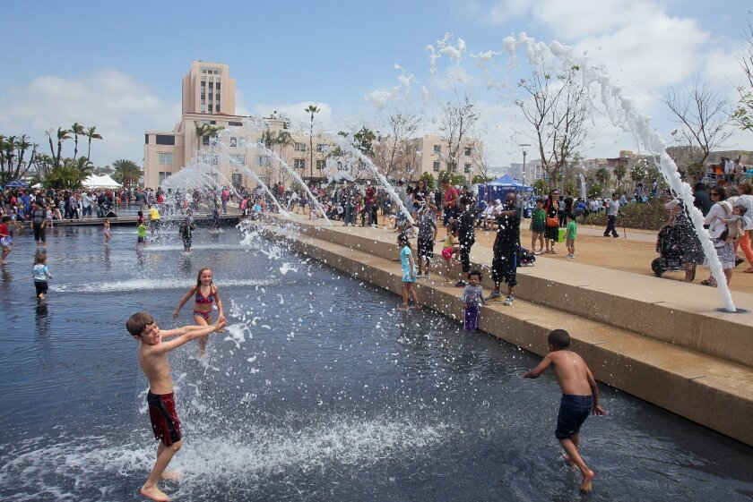 Children play in the new County of San Diego Waterfront Park adjacent to the County Administration Building shown above at left.