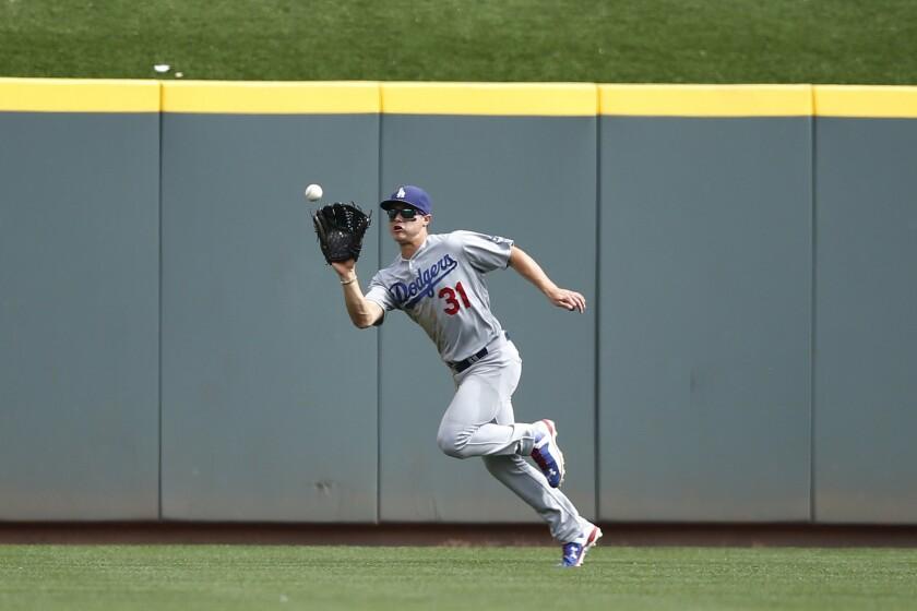 Dodgers center fielder Joc Pederson makes a running catch to snag a ninth inning fly ball against the Reds.