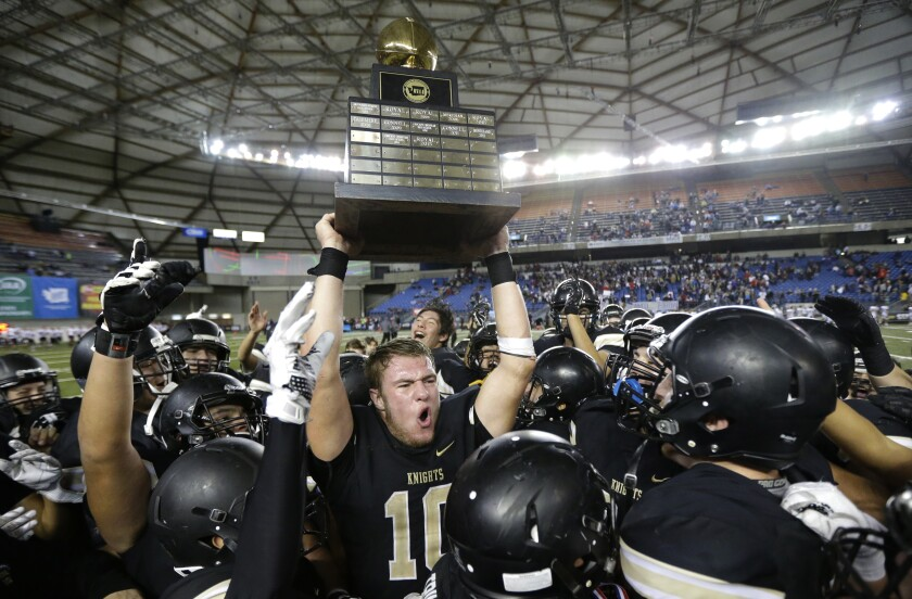 FILE - In this Dec. 3, 2016 file photo, Royal quarterback Kaden Jenks (10) celebrates with the trophy after Royal beat Connell in the Washington Div. 1A high school football championship in Tacoma, Wash. The overwhelming uncertainty of whether high school sports can go forward in the fall of 2020 amidst the continued COVID-19 pandemic is a constant refrain among administrators and decision makers as the clock ticks closer to the start of the 2020-21 school year with little clarity in place for an obvious and safe path moving forward for athletics. (AP Photo/Ted S. Warren, File)