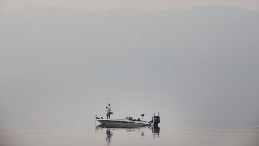 CLEARLAKE OAKS, CALIF. -- WEDNESDAY, AUGUST 8, 2018: A man is fishing in Clear Lake as the smoky haz