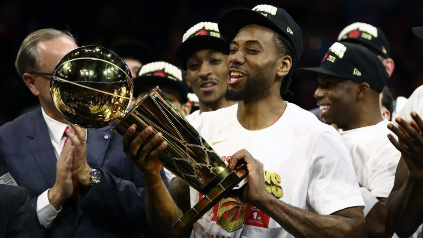 Toronto Raptors' Kawhi Leonard celebrates with the Larry O'Brien Championship Trophy after his team defeated the Golden State Warriors in Game 6 to close out the NBA Finals in Oakland on June 13.