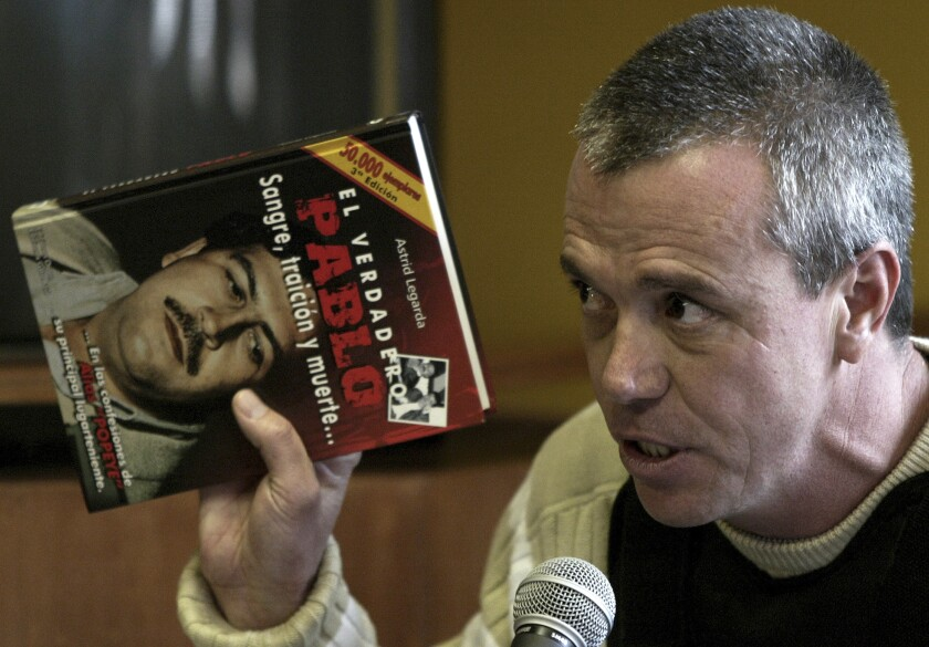 """In June 27, 2006, Jhon Jairo Velasquez, a former hit man for Pablo Escobar, testifies while holding a book titled """"The True Pablo, Blood, Treason, and Death"""" during the trial against Alberto Santofimio Botero in Bogota, Colombia."""