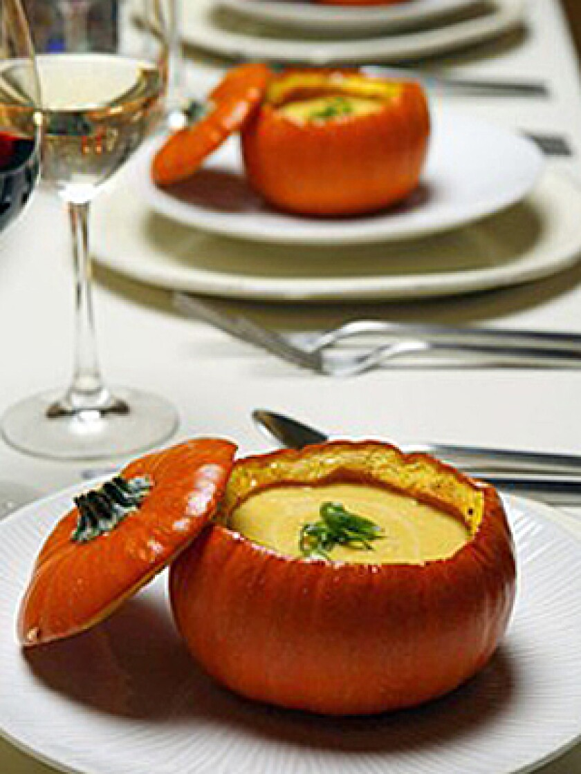"""IMPRESS YOUR GUESTS: Serve spiced pumpkin soup with maple syrup inside roasted pumpkins. Total time: 2 hours Servings: 12 Note: From Noelle Carter. Grade B maple syrup is preferred for this recipe; it has a richer flavor and is not as highly filtered as Grade A. The mini pumpkins can be roasted several hours ahead. Place the roasted pumpkins in a 250-degree oven for 5 to 10 minutes to warm them before filling. 2 poblano chiles 4 tablespoons butter, divided 12 mini (12- to 16-ounce) pumpkins Fine sea salt Freshly ground black pepper 5 pounds pumpkin such as Sugar Pie or American Pie (2 small or 1 medium) 4 ounces apple wood-smoked bacon, about 3 thick slices, cut into 1/4 -inch dice 1 large onion, cut into medium dice 1/4 cup dry white wine 6 to 7 cups chicken broth, divided 1/2 teaspoon Hungarian paprika 1 teaspoon New Mexico chile powder 1/2 cup maple syrup, divided 1 1/2 cups heavy cream Tabasco sauce to taste 1 bunch green onions , green parts thinly sliced crosswise, the rest set aside for another use 1. Heat the oven to 425 degrees. 2. Roast the poblano chiles over high heat on a rack on your stove-top burner. When the skin is charred all over, place the peppers in a paper bag. Leave them for about 10 minutes, then remove and peel the skin -- do not rinse. Discard the stem and seeds, and chop the peppers coarsely. Set aside. 3. Prepare the pumpkins: In a small saucepan, melt 2 tablespoons butter over low heat. Remove from the heat and set aside. Cut the top quarter off of each of the 12 pumpkins, as if you are making jack-o'-lanterns, but make the hole wide enough for the pumpkin to work as a soup bowl. 4. With a spoon, clean out, then discard the seeds and pulp. Save the stemmed tops; these will work as """"lids."""" Lightly brush the melted butter onto the inside of each pumpkin and the underside of each top. Lightly season the inside of each pumpkin and the underside of each top with salt and pepper. 5. Place the pumpkins cut-side up on a parchment-lined baking sh"""