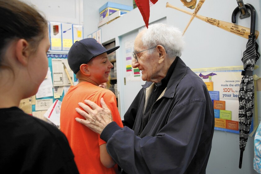 Mel Feuer gets a hug from Adam Berman on Feuer's last day meeting with fifth-graders at Castle Heights Elementary School. Feuer shares stories about his experiences in WWII and as a prisoner in Stalag 17, as well as his time as a teacher and administrator.