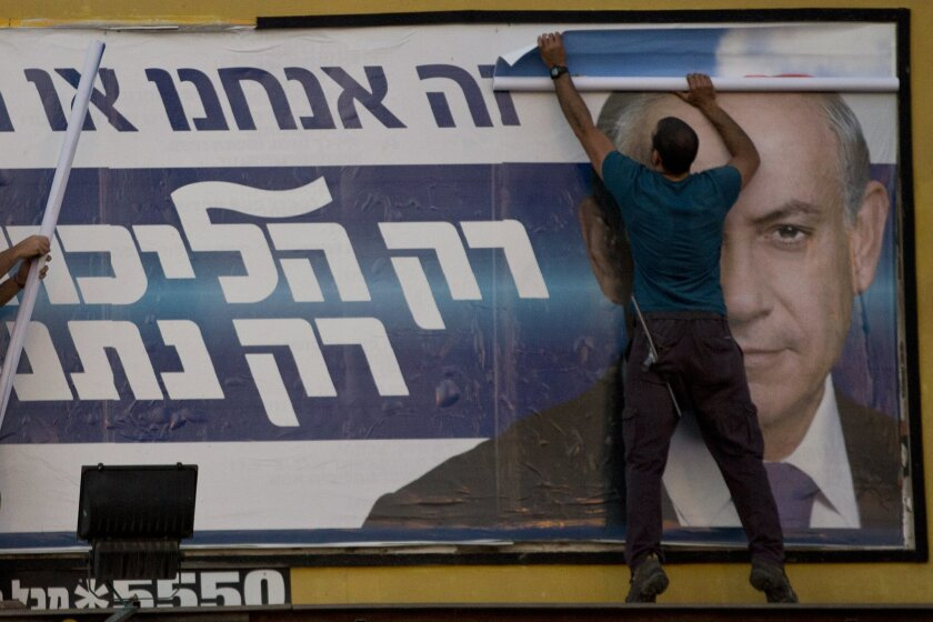 Workers in Israel remove an election campaign billboard showing Prime Minister Benjamin Netanyahu. With the election over, Netanyahu went on U.S. television Thursday to try to walk back several controversial remarks.