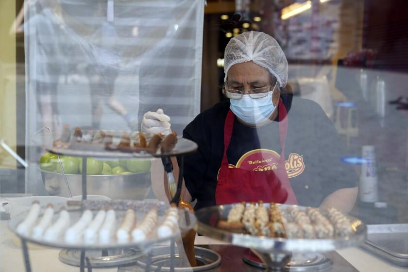 Una trabajadora usa una mascarilla mientras prepara postres en el Universal City Walk