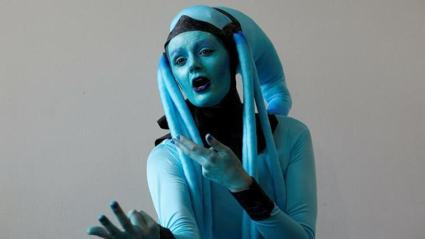 """Leah Thomas, dressed as the character Diva Plavalaguna from """"The Fifth Element"""" movie, poses for a picture as she attends opening day Comic-Con International. (MIKE BLAKE)"""