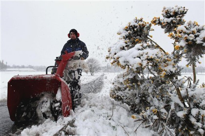 A green-keeper clears snow from paths on the Kings Course Golf Course at Gleneagles in Scotland after more than six inches of snow fell in the space of four hours in parts of Scotland overnight as an Arctic weather front bore down on the United Kingdom Tuesday April 3, 2012. Snow fell in the Scottish highlands Tuesday, just days after record-breaking warm temperatures in northeastern Scotland. The temperature hit 0 Celsius (32 Fahrenheit) that compares to 23.6 Celsius (75 Fahrenheit) last week in Aboyne, Aberdeenshire, a new high in Scotland for the month. (AP Photo/Andrew Milligan/PA Wire) UNITED KINGDOM OUT NO SALES NO ARCHIVE