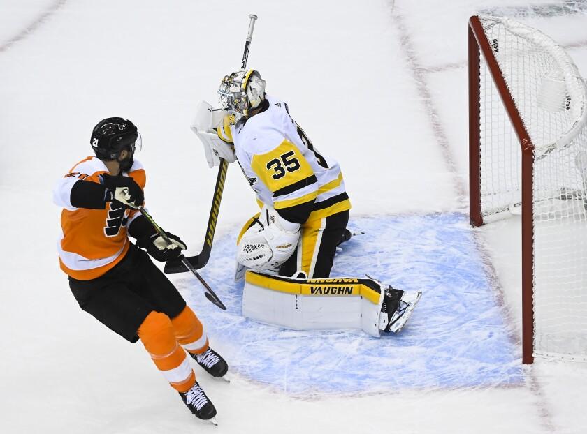Philadelphia Flyers center Scott Laughton (21) scores the game winning goal against Pittsburgh Penguins goaltender Tristan Jarry (35) during overtime in an exhibition NHL hockey game, Tuesday, July 28, 2020 in Toronto. (Nathan Denette/The Canadian Press via AP)