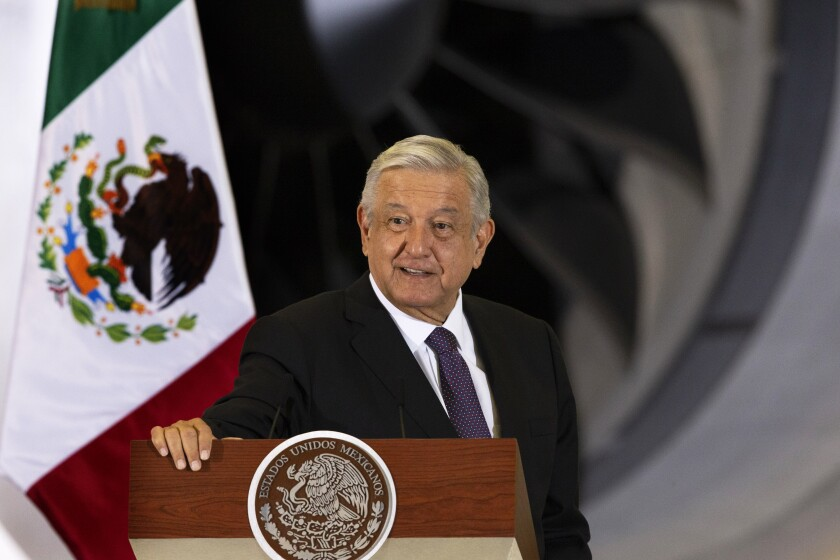 Mexican President Andres Manuel Lopez Obrador gives his daily, morning press conference in front of the former presidential plane at Benito Juarez International Airport in Mexico City, Monday, July 27, 2020. The president, who only flies commercial as one measure in his austerity government, has been trying to sell the plane since he took office. (AP Photo/Marco Ugarte)