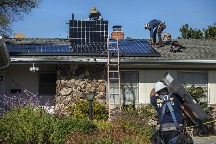 A man carries a solar panel and two others work with tools on a roof to install the panels.