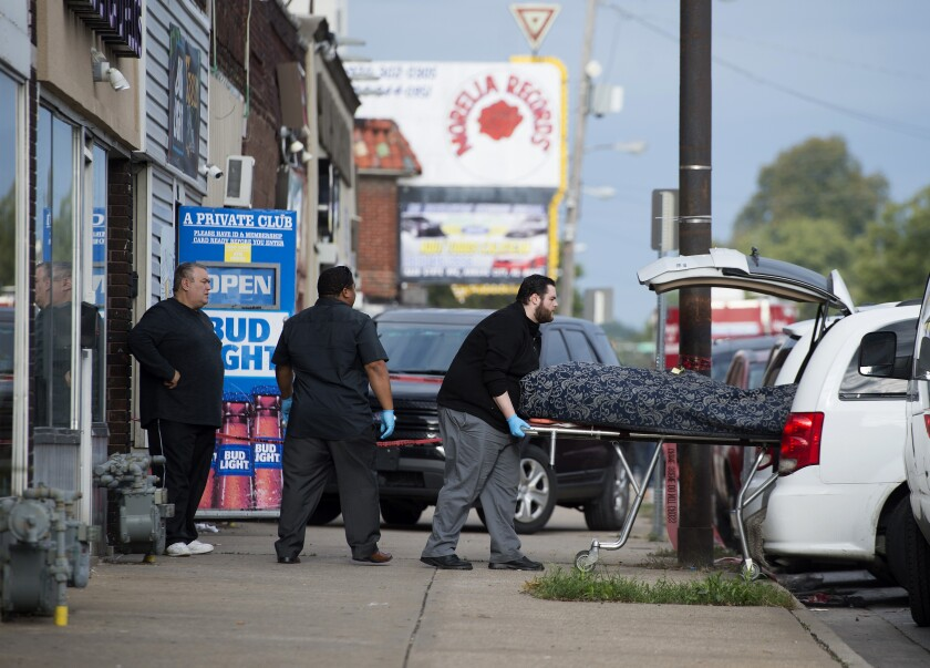 The body of a shooting victim is placed in a coroner's van Sunday outside Tequila KC Bar.