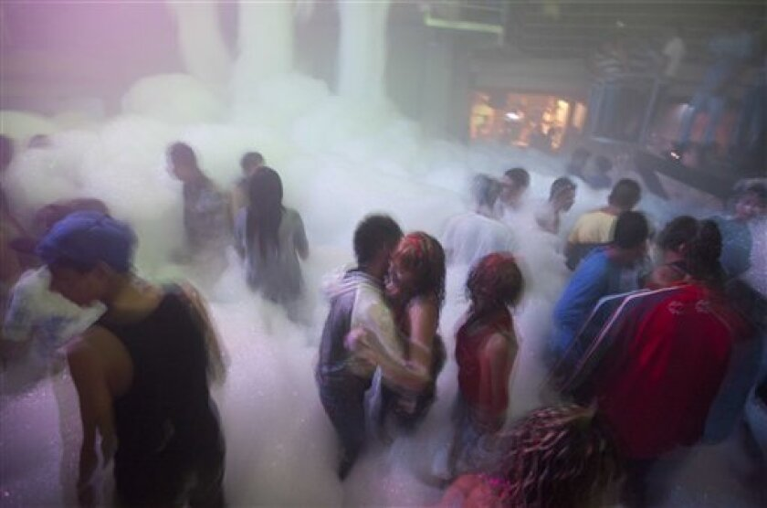 """In this Aug. 24, 2012 photo, youth known as """"reggaetoneros"""" dance at a discotheque in Ecatepec, in a suburb of Mexico City. Thousands of lower-income Mexico City teens have become obsessive imitators of a Puerto Rican subculture based on garish street fashions and the throbbing blend of reggae, hip"""