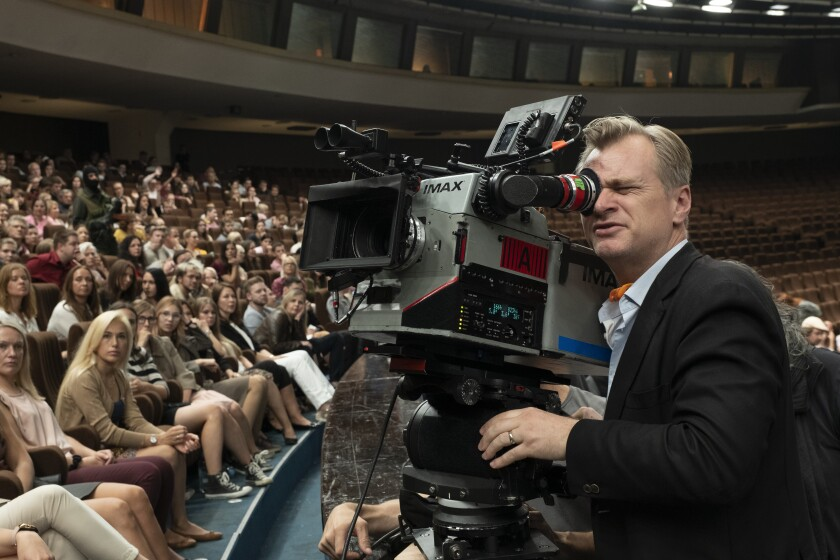 """This image released by Warner Bros. Entertainment shows director Christopher Nolan during the filming of """"Tenet."""" On Tuesday, audiences will finally be able to watch, re-watch and dissect the palindromic spy thriller starring John David Washington, Robert Pattinson and Elizabeth Debicki from the comfort of their home. The film will be available on 4K, DVD, Blu-ray and digital with behind the scenes extras that give a peek into the mind-bogglingly complex process of shooting a large-scale action film. (Melinda Sue Gordon/Warner Bros. Entertainment via AP)"""