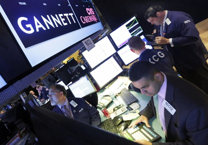 FILE - In this Aug. 5, 2014, file photo, specialist Michael Cacace, foreground right, works at the post that handles Gannett on the floor of the New York Stock Exchange. Tribune Publishing is fighting to stave off USA Today owner Gannett, though it's not immediately clear why. Print ad revenues are