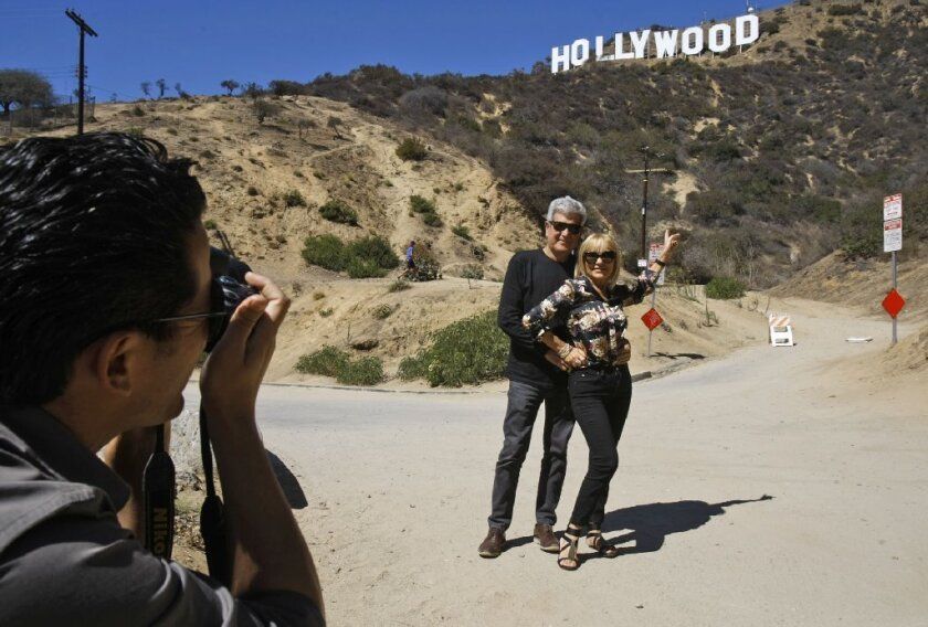 Silvestre Llobet and his wife, Elena Domenech, are photographed by their son, Alejandro, under the Hollywood sign in September 2013 in Beachwood Canyon.