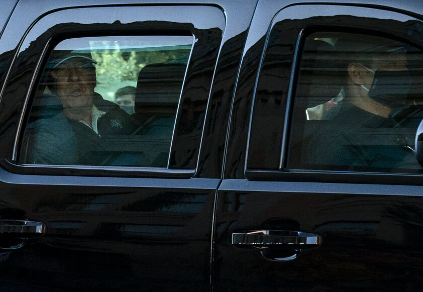 President Trump watches from his presidential state car after playing golf on Saturday.