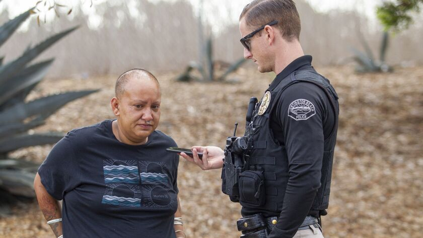 Officer Daniel Chichester lets Yesenia Newell, 30, talk with an acquantence on the phone on Wednesda