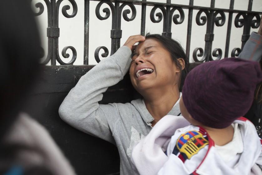 ARCHIVO - En esta fotografía de archivo del 9 de marzo de 2017, un familiar de un joven que residía en el Hogar Seguro de la Virgen de la Asunción llora mientras espera la divulgación de los nombres de los que murieron en un incendio en el refugio, fuera de la morgue donde se identificaban los cuerpos en Ciudad de Guatemala. La organización Disability Rights International dijo el miércoles 13 de octubre de 2021 que los sobrevivientes del incendio aún están en riesgo debido a la falta de protección del gobierno, afirmando que más de 60 de los sobrevivientes han muerto. (AP Foto/Moises Castillo, Archivo)