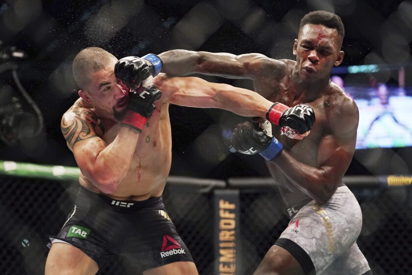 Robert Whittaker of Australia, left, is hit by Israel Adesanya of New Zealand as they compete during UFC 243 in Melbourne, Sunday, Oct. 6, 2019. Interim champion Adesanya dethroned UFC middleweight champion Whittaker with a knockout in the second round of their 185-pound unification bout. (Michael Dodge/AAP Image via AP)NZ