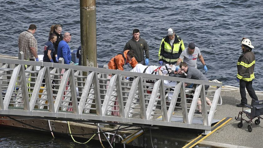 Emergency response crews transport an injured passenger to an ambulance at the George Inlet Lodge do