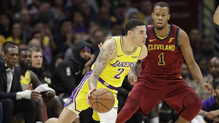Lakers' Lonzo Ball (2) drives past Cleveland Cavaliers' Rodney Hood (1) in the first half of a game Wednesday in Cleveland.