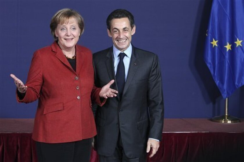German Chancellor Angela Merkel, left, and French President Nicolas Sarkozy, right, pose for a group photo at the European Council building in Brussels, Thursday, Dec. 10, 2009. Western European nations are struggling to convince their poorer eastern neighbors to present a united front on climate change by helping pay developing nations to cut emissions and adapt to climate change. (AP Photo/Geert Vanden Wijngaert)