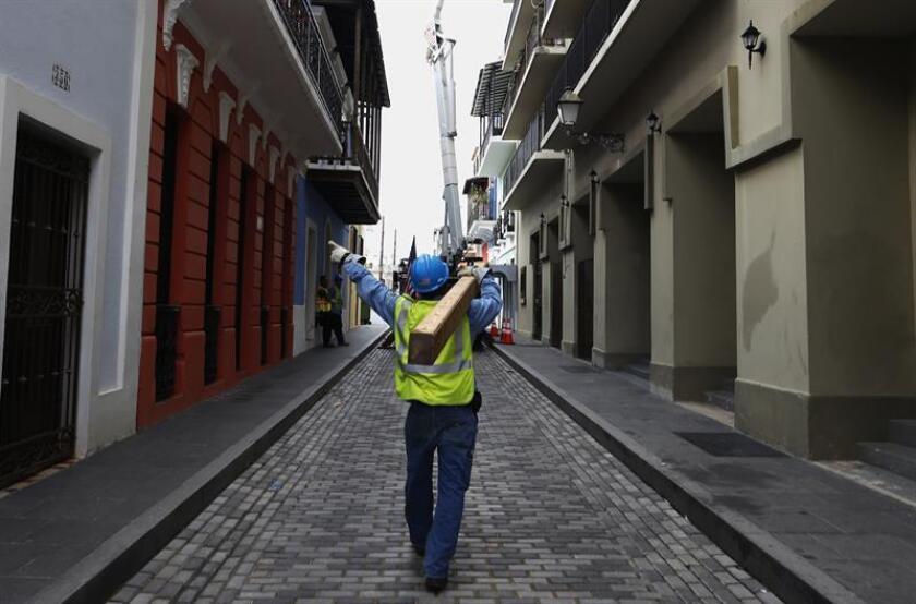 Un empleado de la empresa neoyorquina ConEdison trabaja restableciendo cables de electricidad dañados por el paso del huracán María en el Viejo San Juan (Puerto Rico). EFE/Archivo