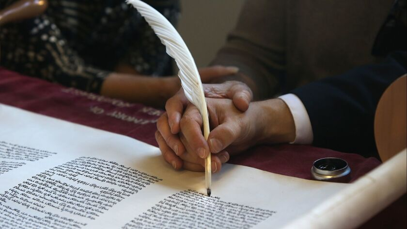 Careful hands write the final letters onto the UC Irvine's Unity Torah during ceremony at the Cross