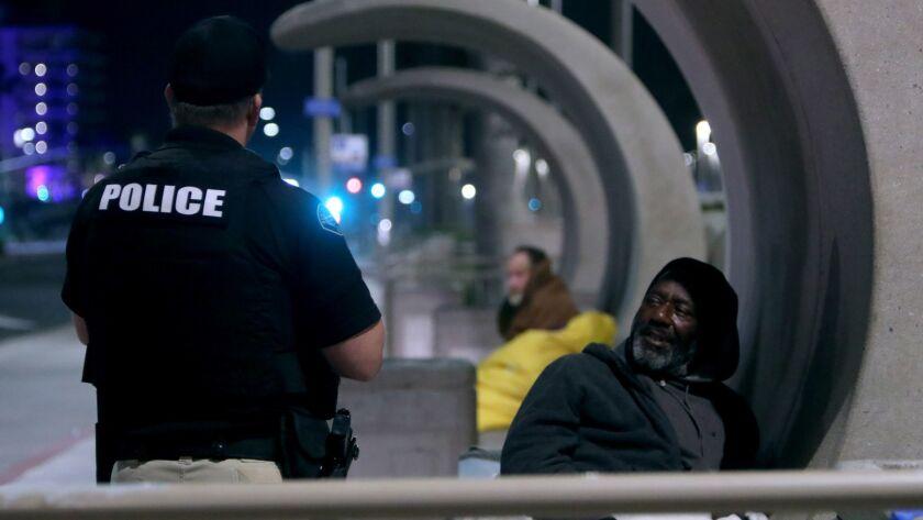 Huntington Beach Police Homeless Task Force officer Gabe Ricci speaks with a homeless man sleeping o