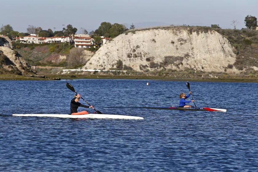 Kayakers paddle through Newport Bay at the Newport Aquatic Center in Newport Beach.