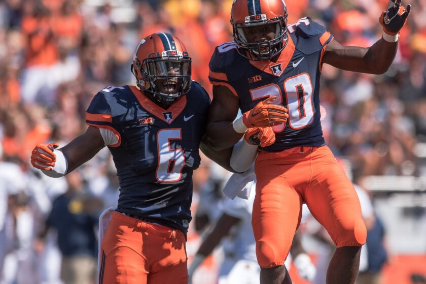 Illinois defensive lineman Carroll Phillips (6) and  defensive back Julian Hylton (30) celebrate Hylton's first quarter interception during an NCAA college football game against Murray State, Saturday, Sept. 3, 2016 at Memorial Stadium in Champaign, Ill.  (AP Photo/Bradley Leeb)