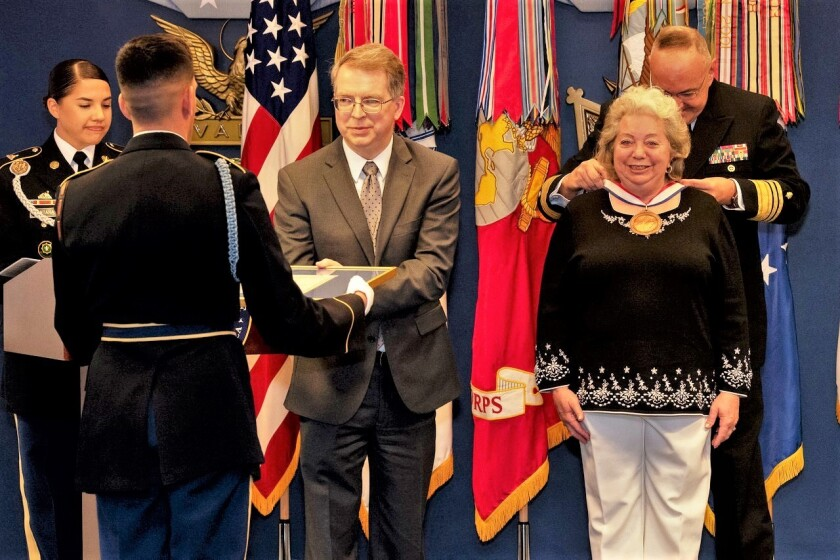 The Navy's 38th Surgeon General Vice Adm. C. Forrest Faison, MC, USN, places the Spirit of Hope medallion around Vicki Miller's neck, and the Deputy Secretary of Defense, Honorable David Norquist, left, presents the framed certificate at a ceremony Sept. 28 at the Pentagon's Hall of Heroes in Washington, D.C. Courtesy of U.S. Department of Defense
