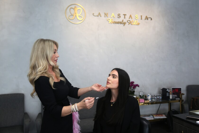 Anastasia Soare, left, works on Gray Tracy's eyebrows to demonstrate how she shapes her clients' brows. Soare's business, Anastasia Beverly Hills, focuses on the golden ratio method to achieve spot-on brows.