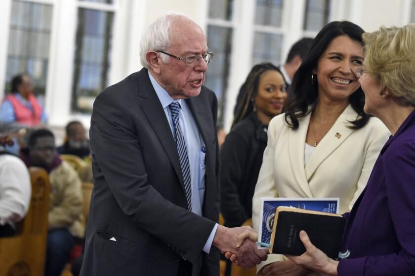 Democratic presidential candidates Sens. Bernie Sanders and Elizabeth Warren shake hands Monday in Columbia, S.C. Rep. Tulsi Gabbard (D-Hawaii) is center.