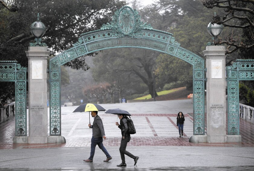 Pedestrians walk in a light rain at UC Berkeley. Another major storm is forecast to soak the Bay Area on Monday.