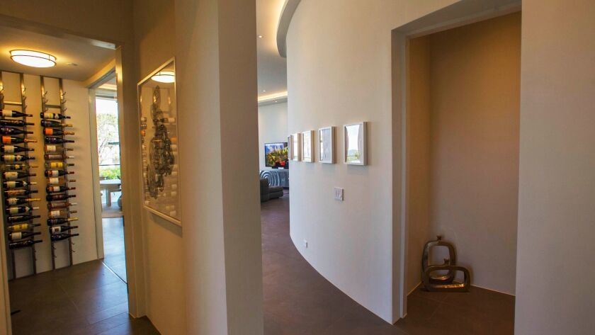 A curved wall that leads in to the living room area with a display wine room that is visible from th