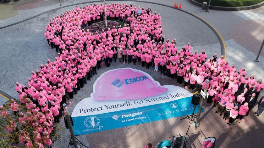Hundreds of New Yorkers wearing pink hard hats and pink shirts form a pink ribbon in honor of Breast