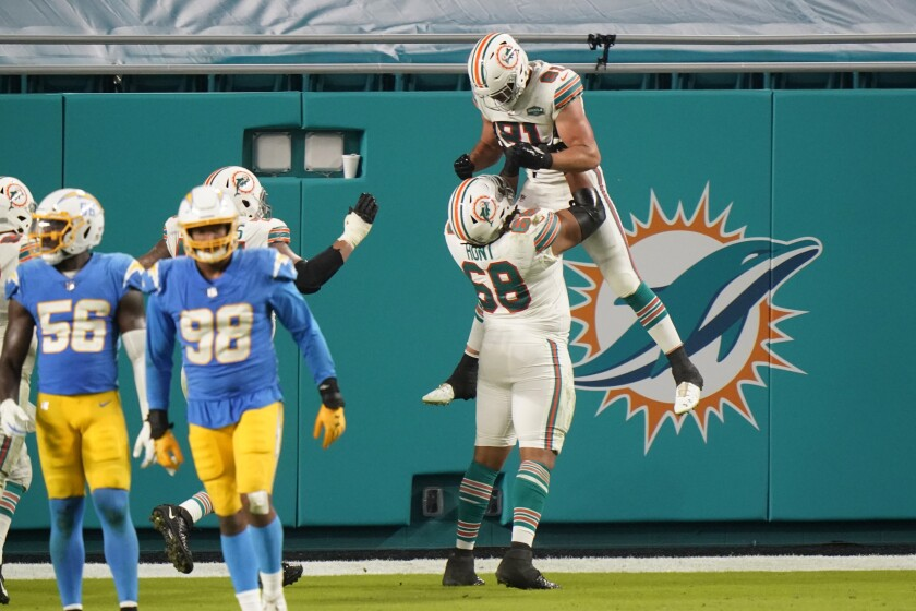 Miami Dolphins offensive tackle Robert Hunt (68) picks up tight end Durham Smythe (81) after Smythe scored a touchdown.