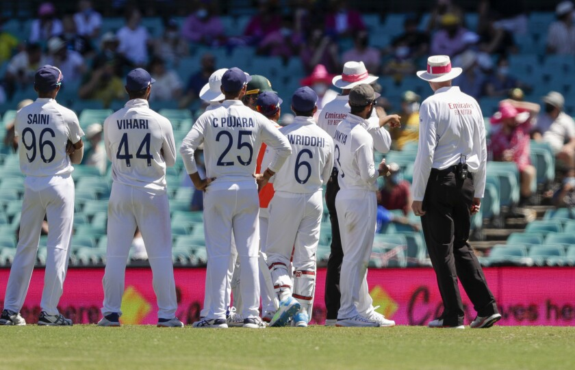 Indian players talk with the umpires after an issue with the crowd during play on day four of the third cricket test between India and Australia at the Sydney Cricket Ground, Sydney, Australia, Sunday, Jan. 10, 2021. (AP Photo/Rick Rycroft)