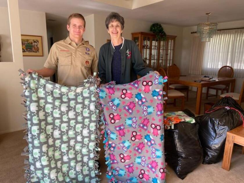 """The Women's Club of Vista has worked with the Vista Community Clinic since 2017, bringing in hand sewn teddy bears for pediatric patients, and plush blankets and knitted hats for newborns. They call their projects """"covers of love."""" So when Boy Scout Ryan Bostwick (now an Eagle Scout) contacted the club looking for a way to help the community as part of his Eagle Scout project, the group suggested making """"Covers of Love"""" for newborn patients at the Vista Community Clinic. Ryan, 16, raised money to buy all of the necessary materials and gathered volunteers to make the soft covers. He and his team made 50 fleece blankets to donate, all with different patterns and colors. From left, Eagle Scout Ryan Bostwick and Women's Club of Vista member, Nancy Ellis. Visit womansclubofvista.org and vcc.org."""