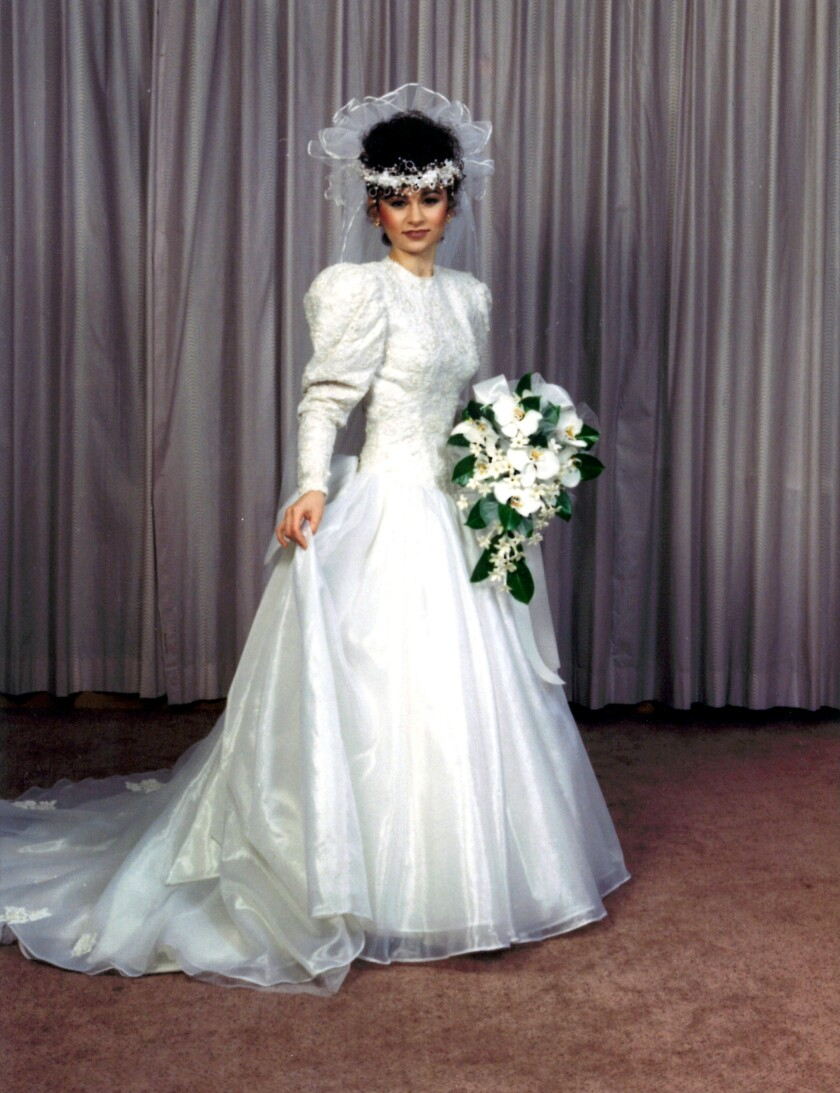 A woman in a long-sleeved white wedding gown.